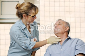 stock-photo-17673204-healthcare-worker-checking-man-s-throat