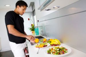 Handsome black man preparing salads in a modern kitchen.
